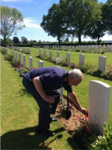 Bob Castles places a Canadian flag at Percival Haney's grave