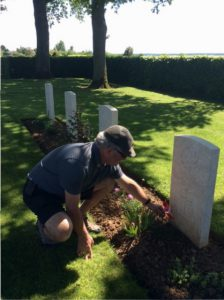 David places flag with poppy at Alex Novinka's grave